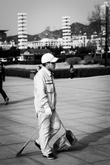 The lonely sweeper (Go-tea 郭天) Tags: dalian xinghai square liaoning dongbei man alone lonely work working busy duty business job clean cleaner cleaning sweep sweeper sweeping uniform cap sun sunny sunglasses portrait canon eos 100d 50mm prime street urban city outside outdoor people candid bw bnw black white blackwhite blackandwhite monochrome naturallight natural light asia asian china chinese shadow pavement brush shovel