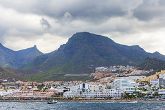 Another view of the coast (Tambako the Jaguar) Tags: buildings houses hotels apartments tourism coast sea boats hills sky clouds tenerife spain nikon d850