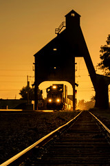 Mile Post 57.75 (Carl's Captures) Tags: coalingtower coalstation coalstage vintage relic history historic silhouette sunset evening goldenhour dekalbillinois uprr unionpacificrailroad genevasubdivision tracks backlight freighttrain stacktrain unittrain eastbound themidwest rural signals semaphores ballast framing transportation summer august dusk cofc containers locomotive headlights arches nostalgia landscape vertical chutes gravity nikond7500 sigma18300 photoshopbyfehlfarben thanksbinexo