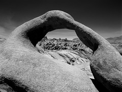 Mobius Arch  (Film) (Harald Philipp) Tags: outdoors rural panorama desolate desolation windswept landscape desert outback natural scenic mountain hill rocks outcrops arch naturalarch holiday vacation tourism tourist exotic destination travel adventure wanderlust beautiful romantic mysterious blackandwhite bw monochrome schwarzweiss grauzone nocolor dark shadows contrast fuji velvia mediumformat 120 film analog analogue filmphotography pentax 645 alien otherworldly daytime unitedstates northamerica usa park nationalpark junelake alabamahills california gunsmoke theloneranger westernusa western movies movielocation hollywoodset movieproduction