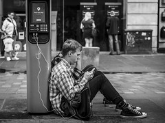 Connected (Leanne Boulton (Away)) Tags: urban street candid portrait streetphotography candidstreetphotography candidportrait streetlife sociallandscape youth young man boy male face expression mobile phone smartphone device technology tech charging cable battery electricity sitting dirt grime pavement tone texture detail depthoffield bokeh naturallight outdoor light shade city scene human life living humanity society culture people lifestyle canon canon5dmkiii 70mm ef2470mmf28liiusm black white blackwhite bw mono blackandwhite monochrome glasgow scotland uk