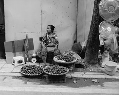 Selling Stuff on the Street (Mondmann) Tags: hanoi vietnam asia southeastasia woman vendor streetvendor vietnamesewoman vietnamese monochrome bw blackandwhite mondmann fujifilmxt10 fruit electricfans street streetphotography candid travel