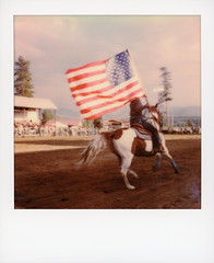 Rodeo Flag Bearer 2 (tobysx70) Tags: polaroid originals color 600 instant film slr680 rodeo flag bearer high country stampede county road 73 fraser colorado co cowgirl horse rider us usa stars stripes old glory galloping motion blur polaradoone polarado 072118 toby hancock photography