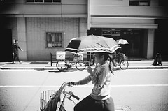 Passing by, slightly out-of-focus... (Eric Flexyourhead) Tags: minamihorie 南堀江 nishiku 西区 osaka osakashi 大阪市 kansai 関西地方 japan 日本 city urban street streetscape cityscape streetscene streetphotography cyclist rider parasol umbrella girl japanese monochrome blackwhite bw ricohgr