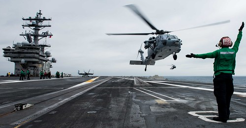 Airman directs an MH-60S Sea Hawk on the flight deck.