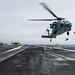 Airman directs an MH-60S Sea Hawk on the flight deck.