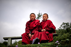 Bhutan: Two young monks attending the Gasa Tshechu. (icarium.imagery) Tags: bhutan canoneos5dmarkiv travel portrait two monks buddhist red dress traditionaldress bench naturallight captureone sigma100400mmf563dgoshsm robe kids children sundaylights