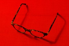 Glasses on a red background (Yirka51) Tags: linen cloth canvas multifocal dioptre diopter spectaclefeet spectacleframes hinge eyeglass eyeglasses glasses table showthrough show shadow screw red plastic glass desk