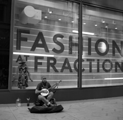 fashion-fraction (kaumpphoto) Tags: rolleiflex 120 tlr ilford bw black white urban city street bango music musician dummy window fashion fraction letters sign mannequin dress hat hand jug bandana sidewalk minneapolis feet