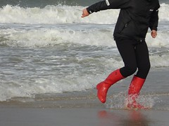 Playing with the waves (willi2qwert) Tags: rubberboots rainboots regenstiefel gummistiefel gumboots girl gummistövlar wellies wellingtons women wasser wet water wave watt beach strand nass
