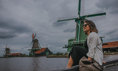 Tilting At Windmills (Mark Liddell) Tags: zaandam zaanse schans zaanseschans holland thenetherlands netherlands nederlands capital city europe travel windmills rural scene village traditional architecture trees framing cloudy overcast day sky river stream reflection canal lindsay asian girl woman canadian japanese long hair sunglasses smile people portrait profile sitting pier