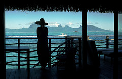 Room with a View  (Tahiti, Film) (Harald Philipp) Tags: outdoors rural panorama seascape landscape natural scenic people silhouette balcony terrace terrasse deck roomwithaview thatchedroof boat airplane hotel villa ocean sea lagoon bay water mountain peak paradise holiday vacation tourism luxury tourist exotic tropical tropics tropicalisland destination travel adventure wanderlust island beautiful romantic mysterious kodak portra 35mm film analog analogue filmphotography primelens kodakretina retinaiiic classiccamera rangefinder antiquecamera foldingcamera day southpacific tahiti pacificocean view