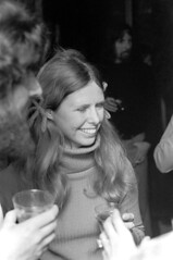 011071 01 (ndpa / s. lundeen, archivist) Tags: nick dewolf nickdewolf blackwhite blackandwhite 35mm film photographbynickdewolf bw january 1971 1970s boston massachusetts unidentified socialevent people woman youngwoman longhair drink drinks cup cups plasticcup plasticcups blond blonde ribbons hairribbons pigtails face smile smiling turtleneck sweater mingling drinking socializing eyesclosed man facialhair beard meetinghousegallery beaconhill artexhibition reception