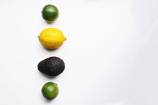 Summer fruits flat lay . Lemons, limes and avocado on white background.Negative space