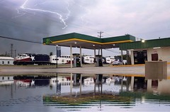 Weather illusion (MoparMadman63) Tags: illusion photoshop transportation transportationsystem train locomotive reflection water lightning thunderstorm overcastskies clouds irvingtx suburb texas intersection street road conveniencestore petrol gasstation
