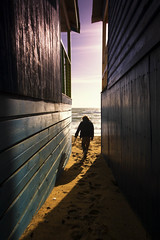Shadow boxing (alideniese) Tags: landscape seascape beach coast shore boy sand afternoon bathingboxes beachboxes buildings light shadow silhouette lines leadinglines sea ocean water bay alideniese mtmartha melbourne victoria australia winter coastal footprints wooden carefree