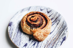 Close up of delicious cinnamon roll in a printed plate. (wuestenigel) Tags: spice cake dessert recipe breakfast brown bread holiday swirl rolls delicious homemade buns spiral fresh traditional view sugar cinnamon wooden baking pastries parchment baked pastry gourmet sticky tasty background plate snack bun dish top sweet food bakery roll paper dough raw