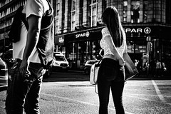 Adjustment needed (Kieron Ellis) Tags: woman jeans bag man people ring hair walking road pavement cars traffic candid street blackandwhite blackwhite monochrome