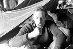 052570 01 (ndpa / s. lundeen, archivist) Tags: nick dewolf nickdewolf may blackwhite photographbynickdewolf tuckerman ravine tuckermanravine whitemountains whitemountain nationalforest mtwashington mountwashington bw nh 1970 1970s newhampshire monochrome blackandwhite shelter camp campground man johnnorton pipe pipesmoker pipesmoking sweater tarp