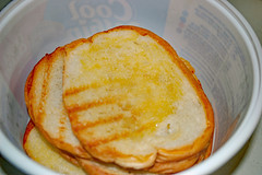 Toasted Garlic Bread. (dccradio) Tags: lumberton nc northcarolina robesoncounty indoor indoors inside food eat meal supper dinner lunch toast bread garlictoast garlicbread buttered container plasticcontainer coolwhipcontainer toasted