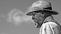 Sunshine and Straw Hats (Neil. Moralee) Tags: neilmoralee steamrally2018neilmoralee man face hat shadow panama straw sunshine old mature wrinkles beard portrait lpov cloud dapple dappled light hot shirt close black white bw bandw blackandwhite mono neil moralee olympus omd em5 sky people elderly summer natgeofacesoftheworld
