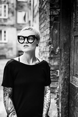 (uerbe) Tags: monochrome mono black blackandwhite blackwhite portrait people woman face eyes eyewear glasses street alley dress expression tattoo tattoos tattoed pierced