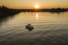 Ahhhh Summer (Terry L Richmond) Tags: water river sunset lake sun reflection dawn boat sky dusk evening tree landscape outdoor outdoors waterway traveling leisureactivities land track marsh going boating sunlight watercraft nature horizon fishing