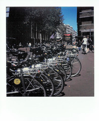 Bikes of Amsterdam (gooey_lewy) Tags: polaroid sx70 instant film photo photography sx 70 road sky amsterdam netherlands holland europe nederlandse dutch cycle bicycle bike rack store park locked up street city