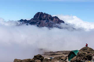 Mount Mawenzi in the background covered by clouds. Mussa checking the internet at 4800m