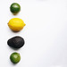 Summer fruits flat lay . Lemons, limes and avocado on white background.Negative space.jpg