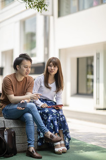 Young couple taking break under tree on street