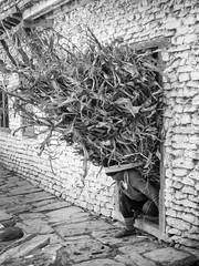 Big Load (newzild) Tags: annapurna circuit trail village man nepal mountains load carry weight cobblestone brick black white bw asia twigs bracken branches head doorway