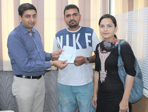 Gurvinder Kang (Director of West Highlander) handing over New Zealand Dependent Work Visa to Rajdeep Singh