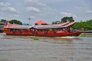 Tour boat passing Koh Kret island on the Chao Phraya river near Bangkok, Thailand