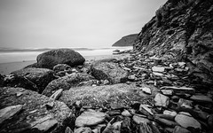 Over rocks and stones (NikNak Allen) Tags: mawganporth cornwall beach bay coast sand rock rocks stone stones cliff cliffs sea water ocean smooth surf waves sky seascape landscape grey greys black white blackandwhite longexposure light shadows low early morning