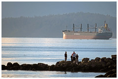 Bayside conversation (HereInVancouver) Tags: men conversation rocks water freighter ocean pacific englishbay vancouver bc canada candid forest mountain canong3x thingstodobythewater vancouverswestend ngc