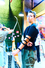 Archery 07 (C & R Driver-Burgess) Tags: bow arrow range draw string fletch aim protective clothing gear strap assistant chest protector pluck finger guard sights indoors mother son family child preteen young teen woman buckles forearm tighten pull boy