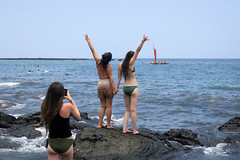 greet the day (BarryFackler) Tags: hawaii hawaiiisland hawaiicounty hawaiianislands polynesia 2018 bigisland tropical kona konacoast sea ocean pacific saltwater coast beach seawater pacificocean bay waves rocky lavarock girls women salute honaunaubay honaunau honaunaubeachpark southkona beachpark canoe photograph pose posing photography tourists visitors boat bikini butt horizon pahoehoe barefoot shoreline coastal shore littoral coastline people holdinghands scene westhawaii outdoor barryfackler barronfackler outdoors