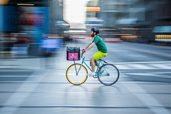 High speed delivery (HisPhotographs.com) Tags: panning toronto city motion speed fast bike foodora downtown ontario canada bicycle colorful fooddelivery service man buildings street streetphotography singlespeed action slowshutter fixy fixie