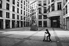 The little girl riding a scooter (dono heneman) Tags: rue street place petitefille littlegirl trottinette scooter riding architecture art ville city urban urbain urbaine noiretblanc nb blackwhite immeuble batiment building fenêtre window porte door sculpture statue ciel sky lumière light paris îledefrance france pentax pentaxart pentaxk3