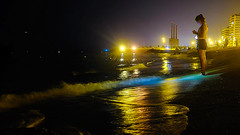 On the waves (Fnikos) Tags: sea water waterfront seashore beach shore sky light reflection colour color rock city building construction tower night nightview nightshot people outdoor