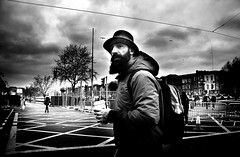 En Route (Owen J Fitzpatrick) Tags: ojf people photography nikon fitzpatrick owen pavement chasing d3100 ireland editorial use only ojfitzpatrick eire dublin republic city tamron candid joe candidphotography candidphoto unposed natural j along bw black white mono blackwhite blackandwhite monochrome blancoynegro pretoebranco photoshoot street 2018 st saint patricks day holiday march 17 festival dubh parade beard man male hat backpack hood coat face burgh quay barrier metal tree cup plastic grid tracery line overcast cloud sky seagull luas