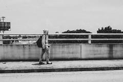 Walk Alone (GRO Photography) Tags: urban railing bridge pedestrian boyntonbeach bw fence hoodie overpass jeans backpack