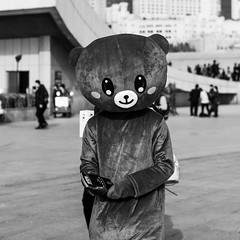 TEDdy talk (Go-tea 郭天) Tags: dalian liaoning dongbei xinghai square teddy bear uniform cute alone lonely busy work working worker adverstising advertisement hot warm sun sunny shadow business portrait fun smile happy hidden hidding hide under cover covered big huge canon eos 100d 50mm prime street urban city outside outdoor people candid bw bnw black white blackwhite blackandwhite monochrome naturallight natural light asia asian china chinese
