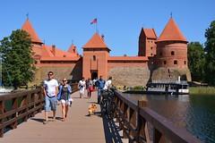 Lithuania / Bridge and Castle of Trakai (Pantchoa) Tags: lituanie europe est pont trakai château architecture eau drapeaux ciel bleu briques gens personnes bois arbres bateau