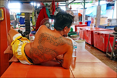 The Man with the Dragon Tattoo - Public Market, Phuket, Thailand (TravelsWithDan) Tags: man inked tattoo relaxing candid streetportrait dragon publicmarket phuket thailand asia canong3x city urban