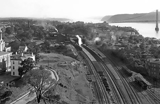 New York Central Hudson line (Water Level Route) to the south, with a steam locomotive & train at the station platform, as seen from the New Haven Railroad Poughkeepsie Bridge, New York State, ca 1942