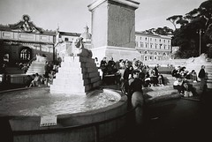 Piazza Del Popolo (goodfella2459) Tags: nikon f4 af nikkor 50mm f14d lens kodak trix 400 35mm blackandwhite film analog piazza del popolo pedestrians people roma fountain water city italy rome bwfp