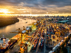 Aerial view of international port with Crane loading containers in import export business logistics with cityscape of modern city at sunset (MongkolChuewong) Tags: aerial aerialview bangkok boat business cargo commerce commercial construction container courier crane delivery distribution dock dockyard drone ecommerce export freight freighters global harbor harbour hongkong import industrial industry international loading logistic logistics port seaport ship shipment shipping shipyard singapore storage structure technology terminal trade transport transportation unloading vessel warehouses krungthepmahanakhon thailand th