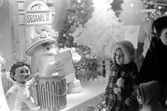 120570 15 (ndpa / s. lundeen, archivist) Tags: nick dewolf nickdewolf photographbynickdewolf blackwhite bw monochrome blackandwhite 35mm film boston massachusetts december 1970 1970s windowshopping windowshoppers store window display windowdisplay oscar storefront departmentstore toy toys holidaydecorations sesamestreet sesamestreetcharacters people children kids child girl woman coat hood hat doll character garbagecan oscarthegrouch sidewalk bigbird